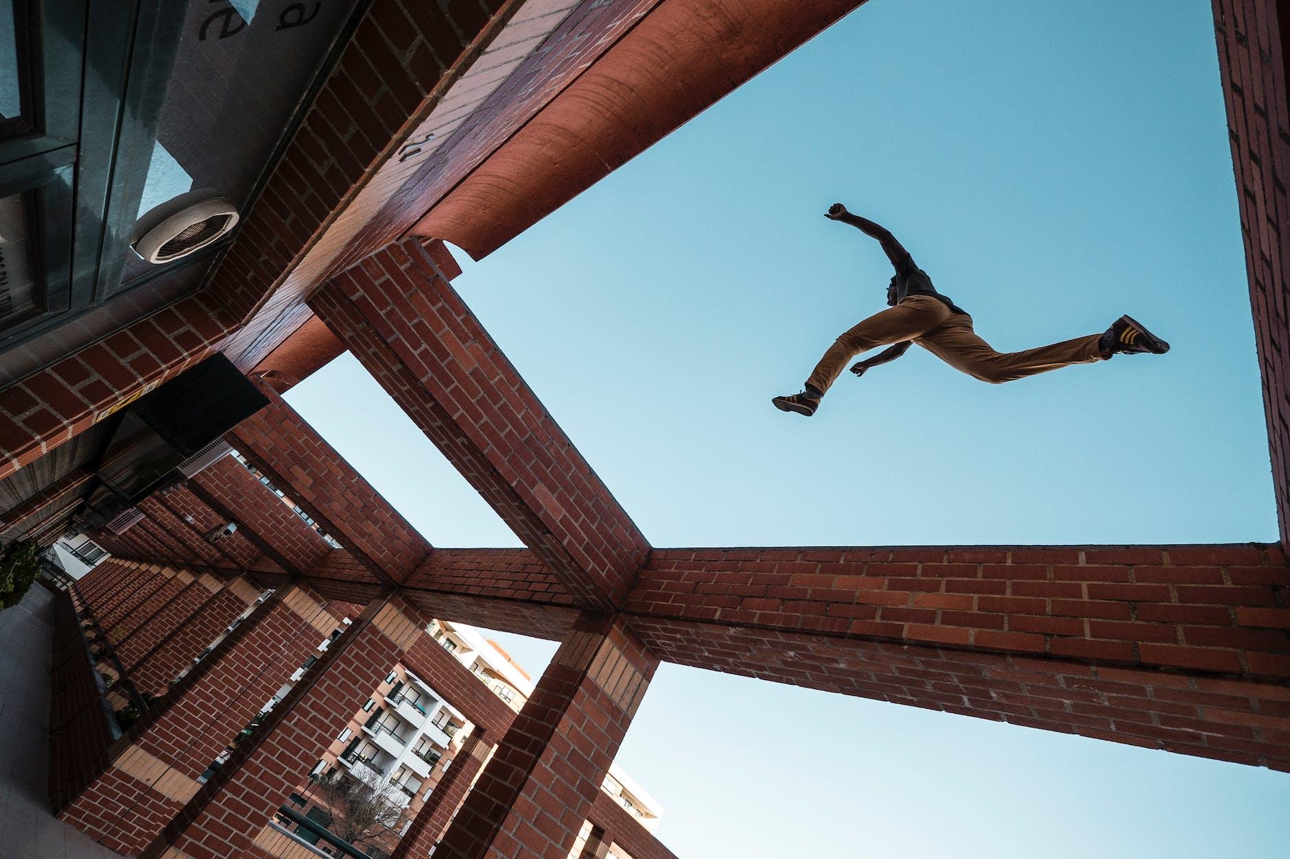 man jumping on high wall bricks