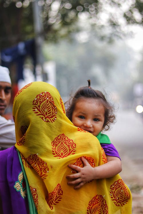 Back view of anonymous woman in colorful shawl on head cuddling adorable content daughter with curly hair looking at camera near crop Muslim father on sidewalk in town
