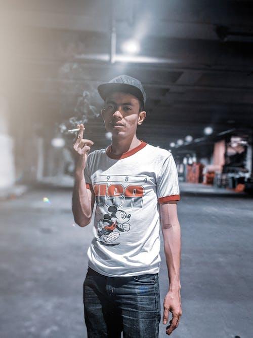 Man Wearing Orange and White Shirt Holding Cigarette Smoking