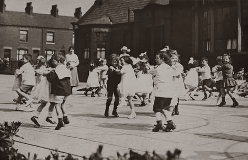 Gray-scale Photo of Children Dancing on Street