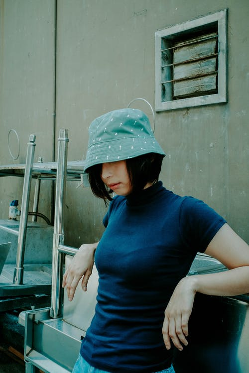 Standing Woman Wearing Gray Bucket Hat and Black Shirt