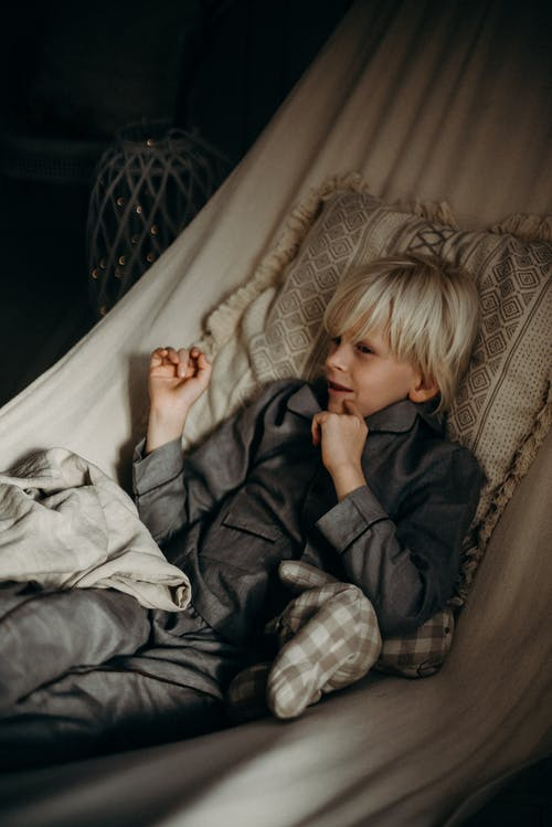 Boy Wearing Gray Collared Button-up Long-sleeved Shirt Lying on Bed