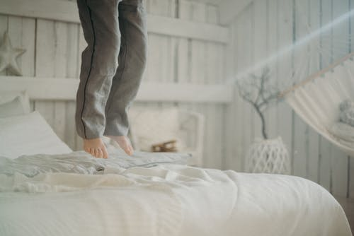 Person Jumping on Bed