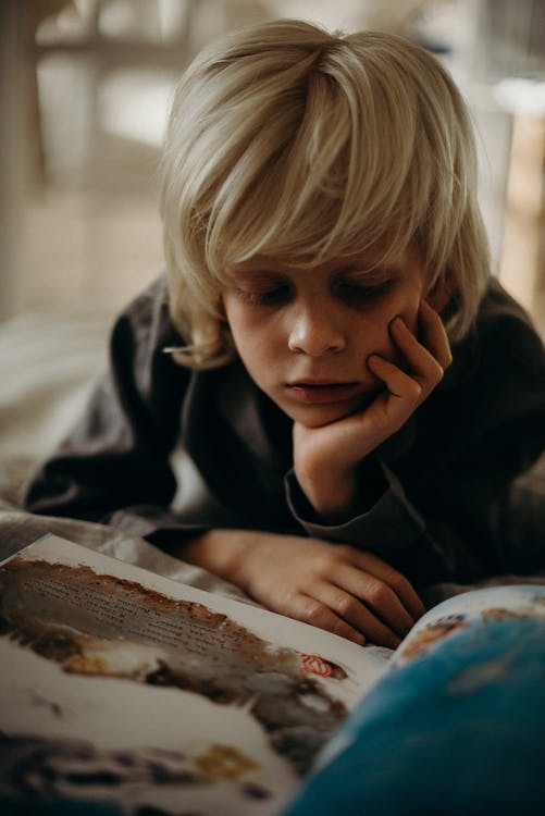 Selective Focus Photography of Boy Resting His Head on His Left Palm