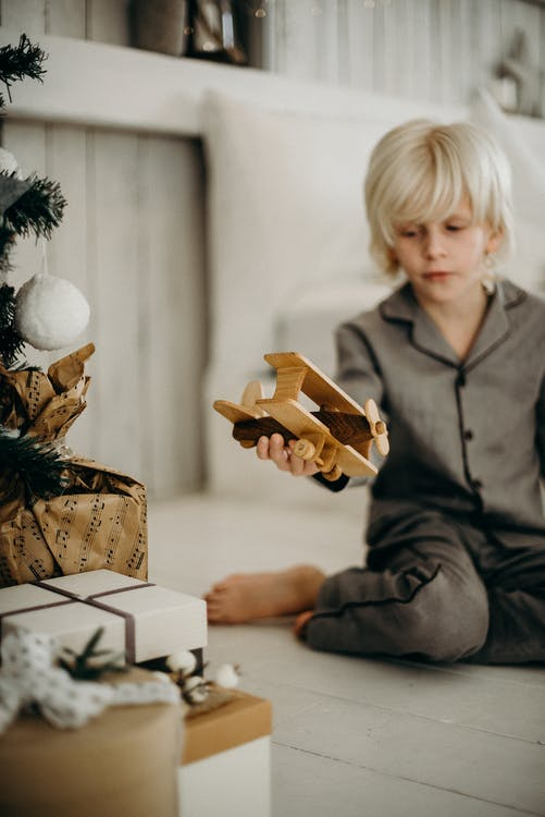 Boy in Gray Pajamas Holding Brown Wooden Plane Toy