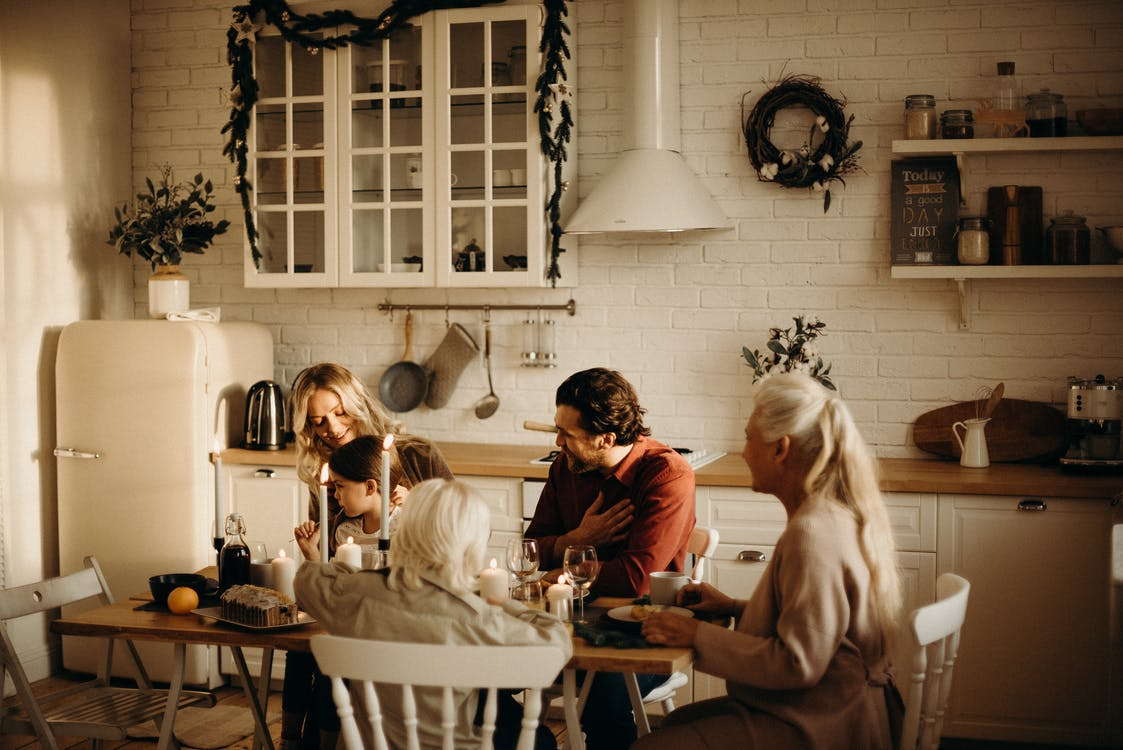 Family Sits on Table Inside Kitchen