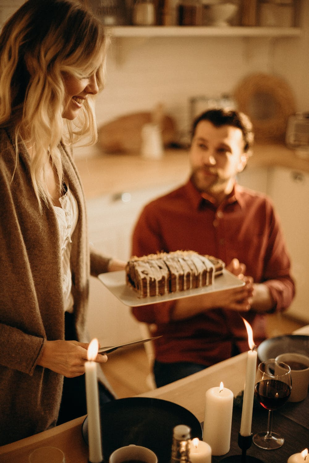 Woman standing while serving cake and the man sitting near a table. | Photo: Pexels