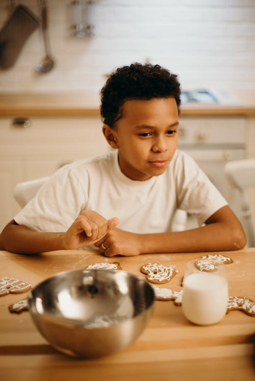 Selective Focus Photography of Boy Beside Table With Cookies