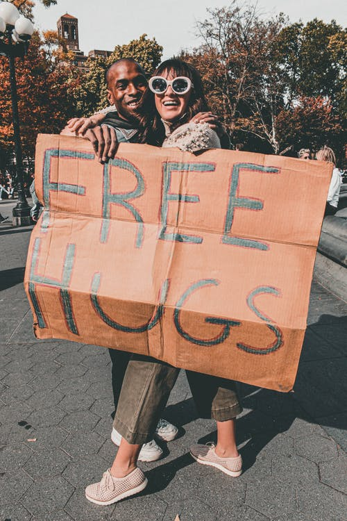 Man and Woman Holding Free Hugs Signage