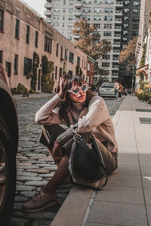 Woman Wearing Brown Turtleneck Sweater Sitting on Street