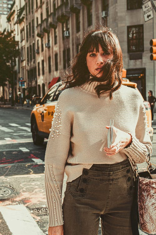 Woman Wearing Gray Turtleneck Sweater and Gray Jeans Posing on Street