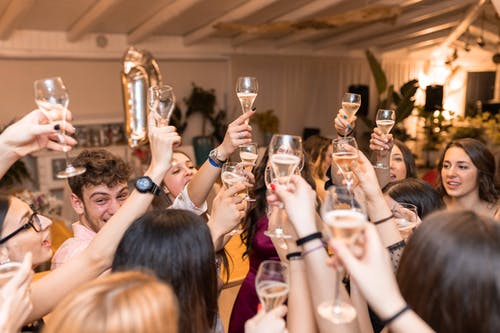 Happy friends clinking glasses with champagne in restaurant