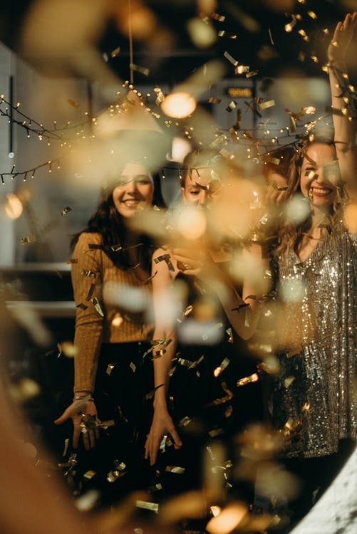 Selective Focus Photography of Smiling Women Standing Behind String Lights