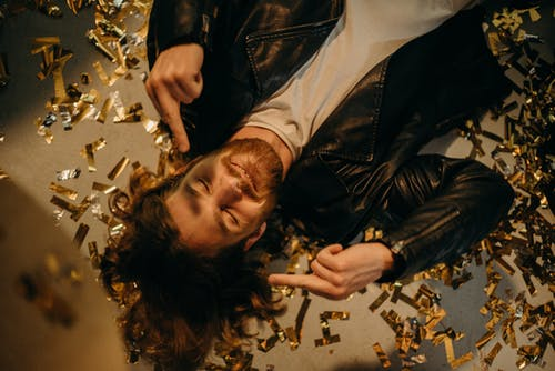 Man in Black Leather Jacket Lying On Floor Covered in Confetti