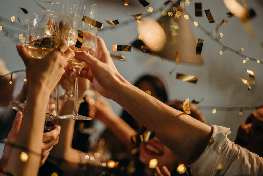 Menschen stoßen mit Weingläsern an.   Quelle: Pexels