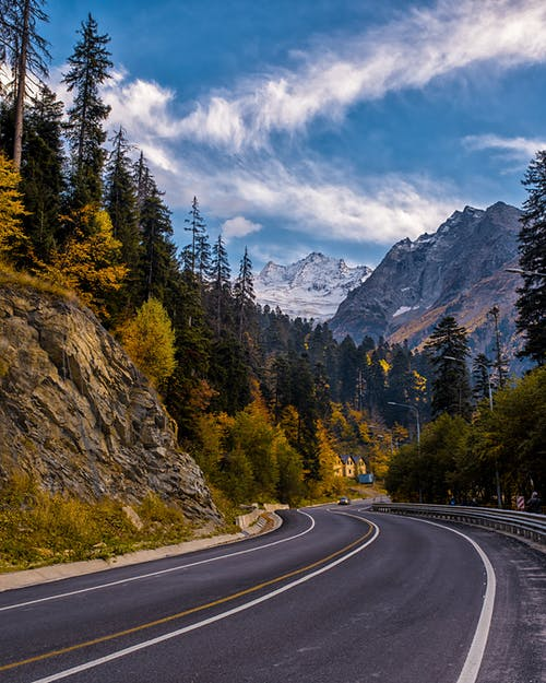 Landscape Photography of Road Between Mountain and Trees