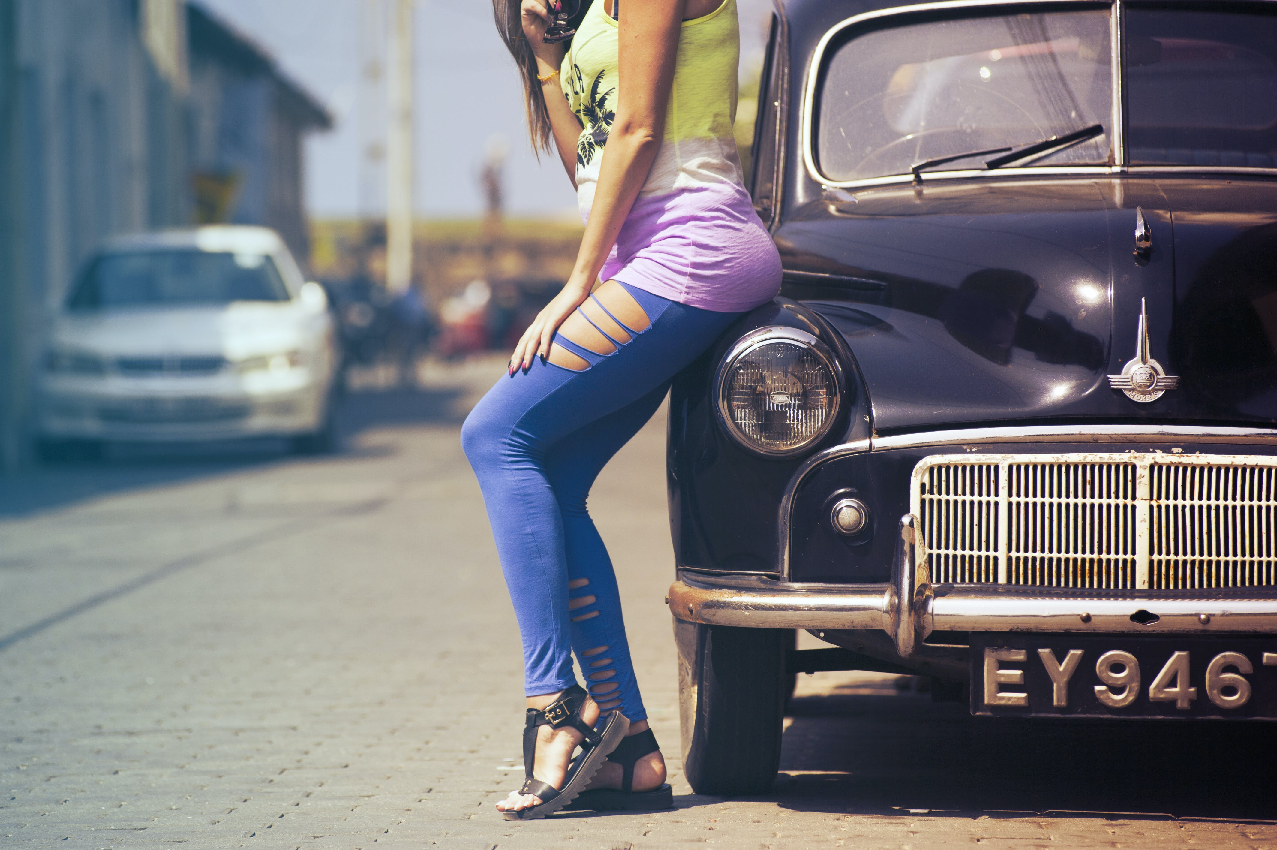 Woman Sitting on Classic Car's Hood