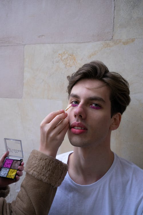 Person Applying Makeup on Man's Face