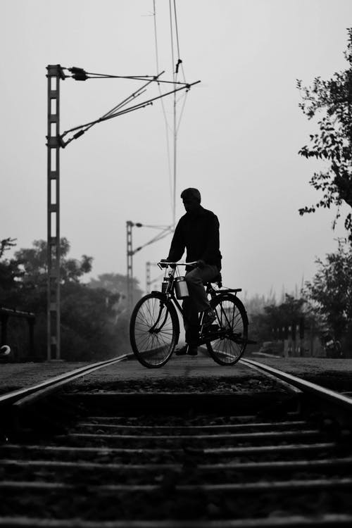 Greyscale Photography of Man Riding on Bike