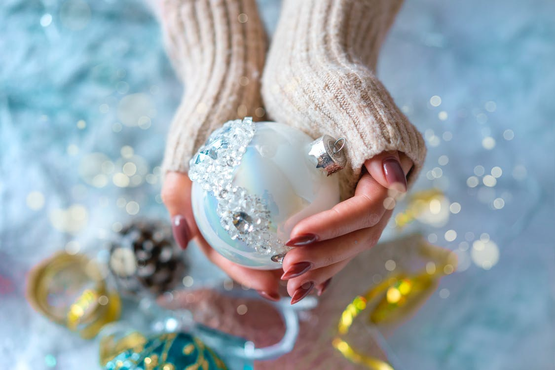 Person Holding White Bauble