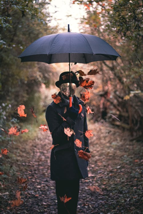 Person Wearing Black Topcoat Holding Black Umbrella