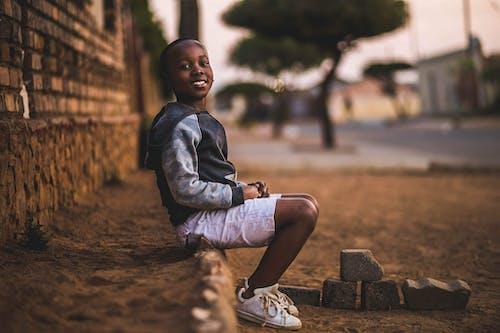 土の上に座っている少年