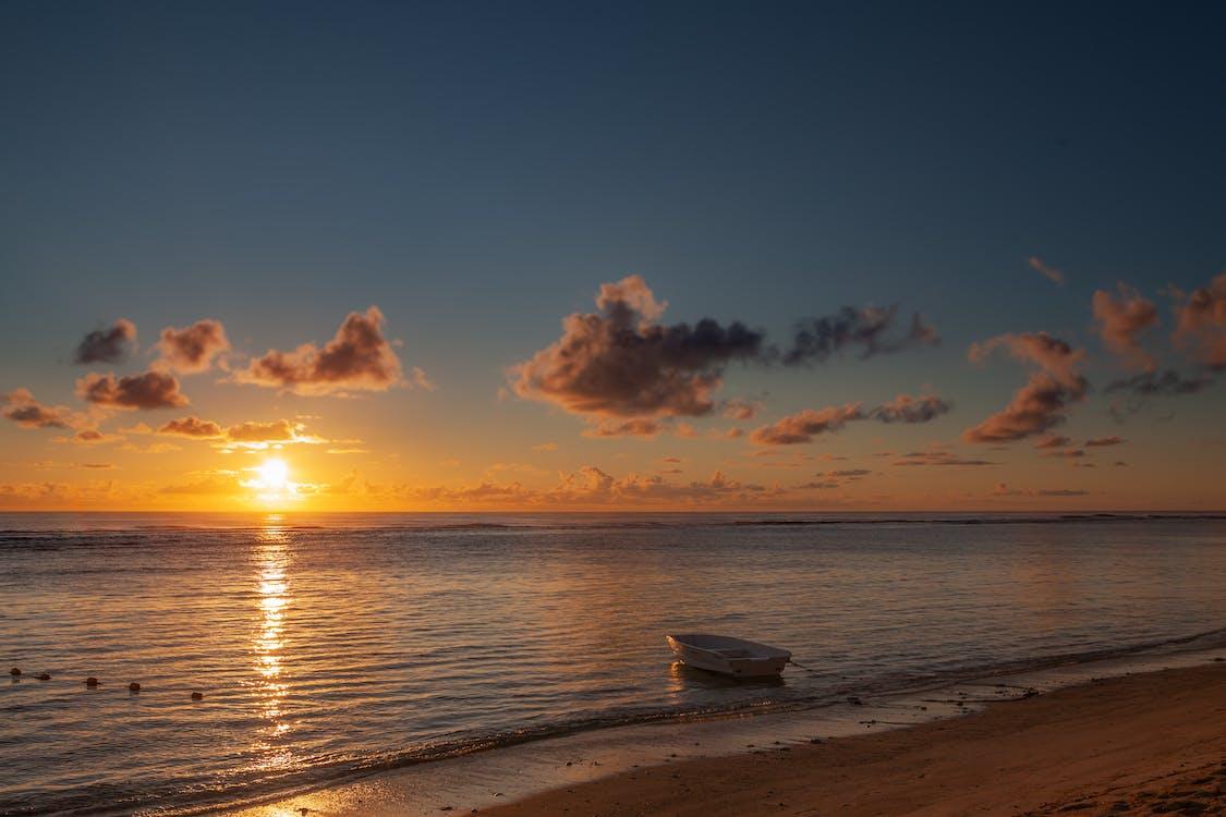 White Boat on Sea Under Orange and Blue Sky during Sunrise