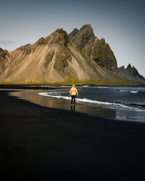 Photo Of Person Standing Near Seashore