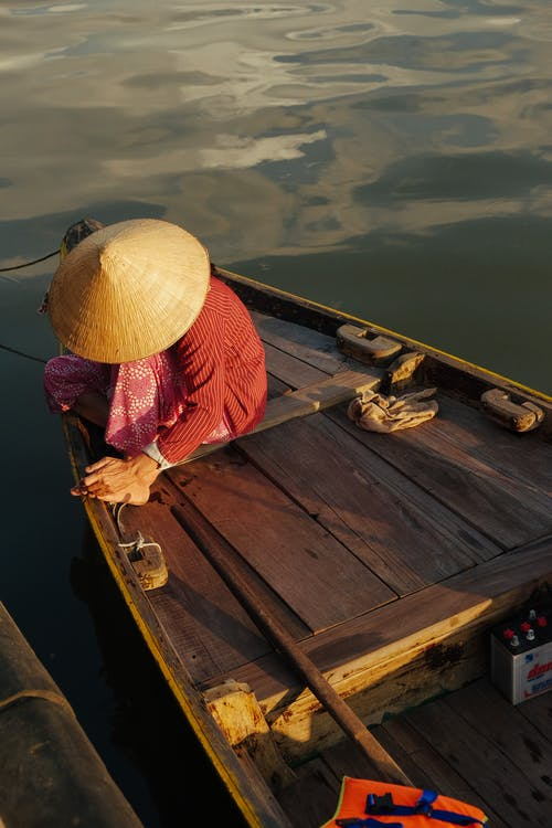 Person Sitting on Brown Wooden Boat