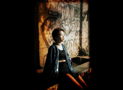 Photo Of Woman Sitting Near Wall