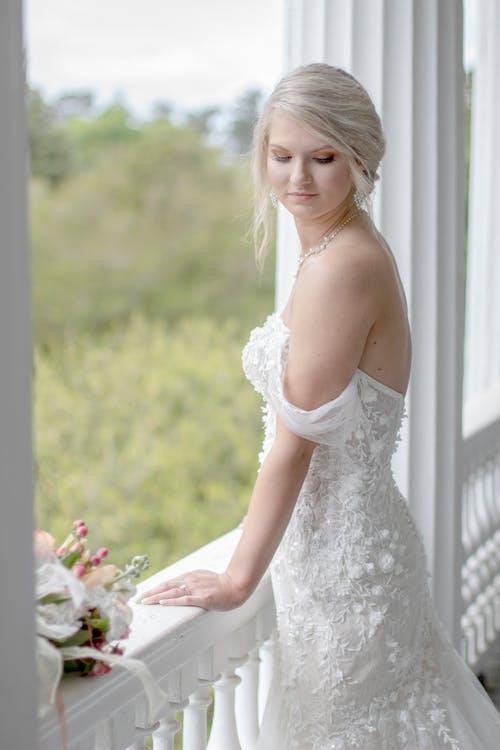 Женщина Носила Белое Свадебное Платье Стоя У Белого Балкона