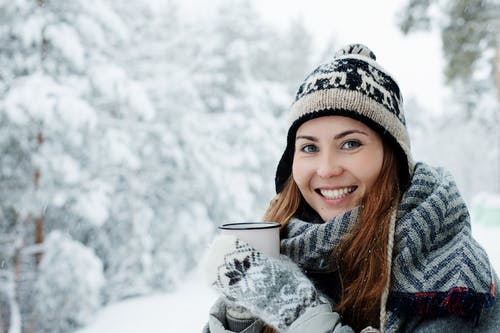 Woman Smiling While Holding a Mug