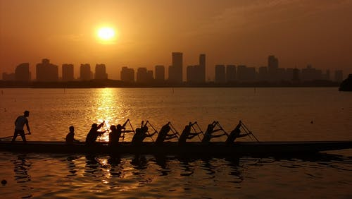 Silhouette of People Riding Canoe on Water during Sunset
