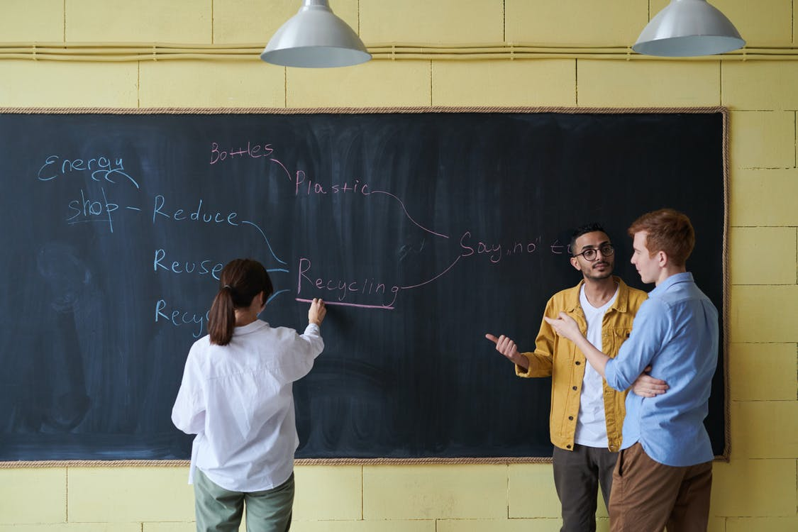 Photo Of Woman Writing On Blackboard