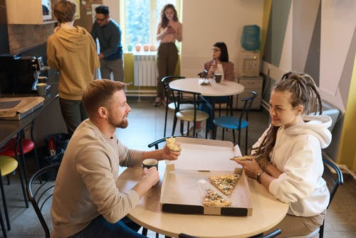 Man and Woman Eating Pizza Indoors