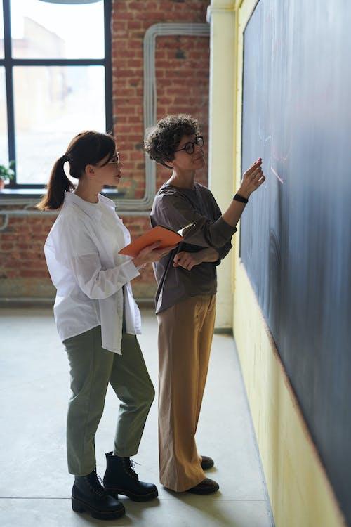 Two Women Standing Near Chalk Board