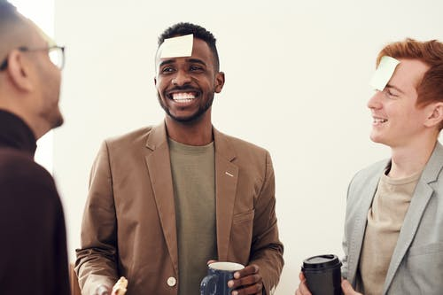 Photo of Men Smiling While Holding a Cup