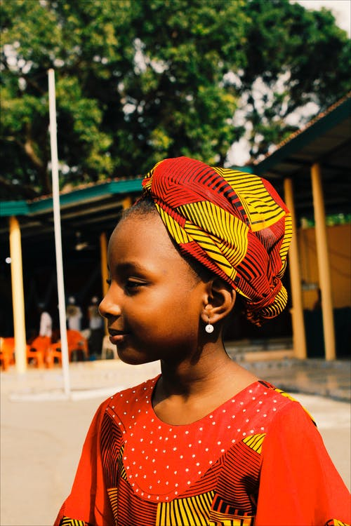 Side View Of A Young Girl Wearing A Colorful Headdress Standing Near A BUilding