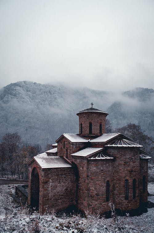 Brown Brick Church Near Mountains In Winter
