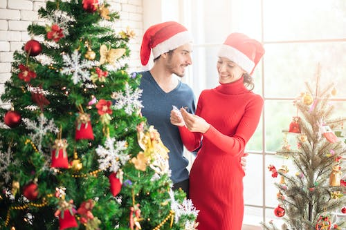 Man and Woman Standing Beside Christmas Tree
