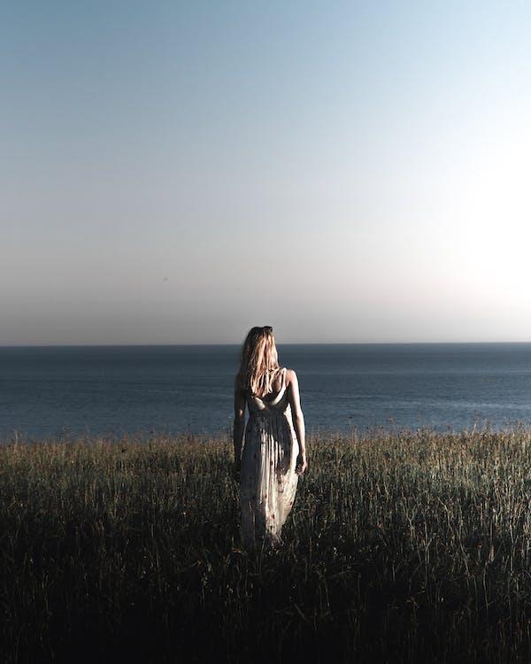 Woman Wearing A Printed Long Dress Walking on Grass Field Near The Sea