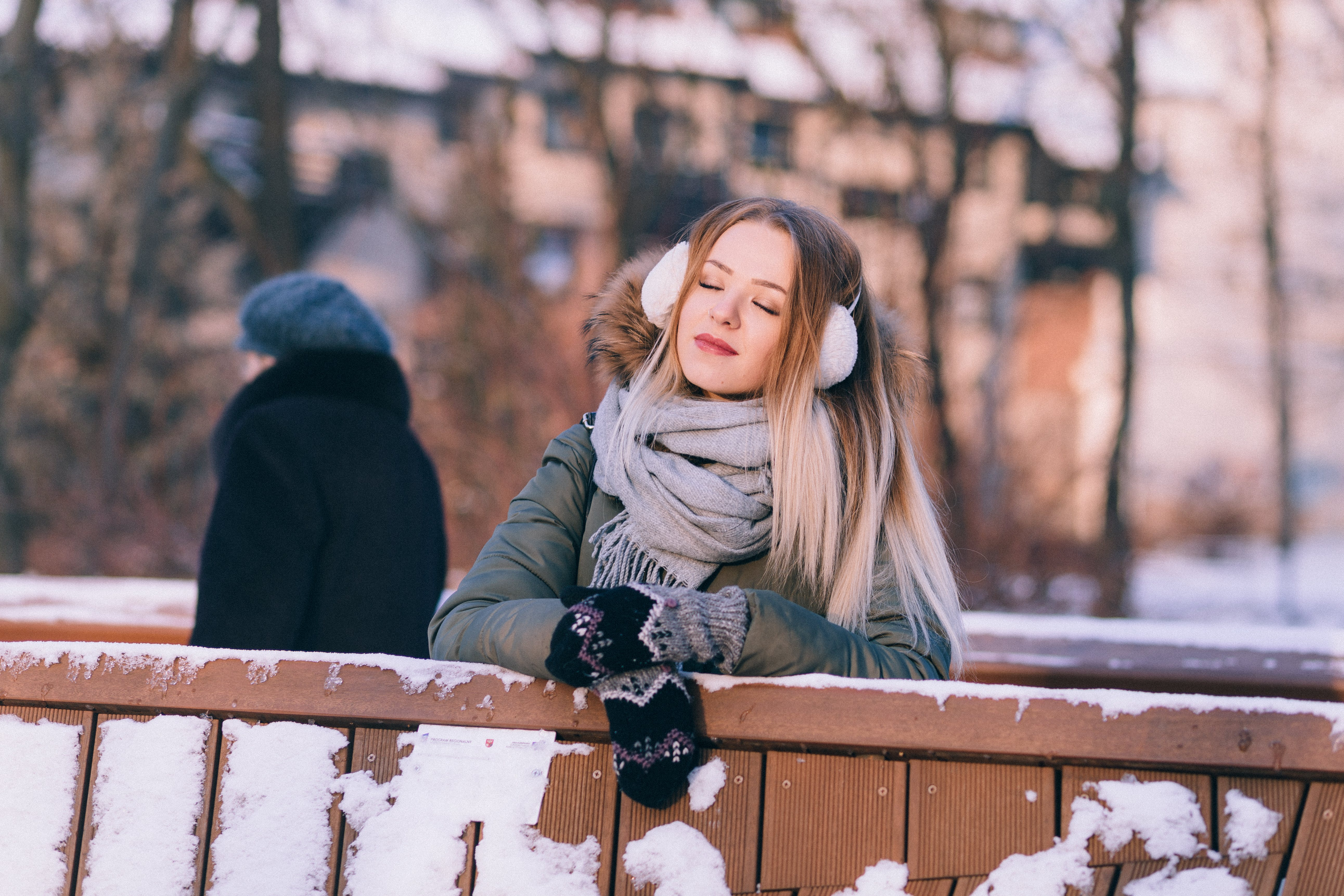 Young Woman Sitting on Bench in Winter