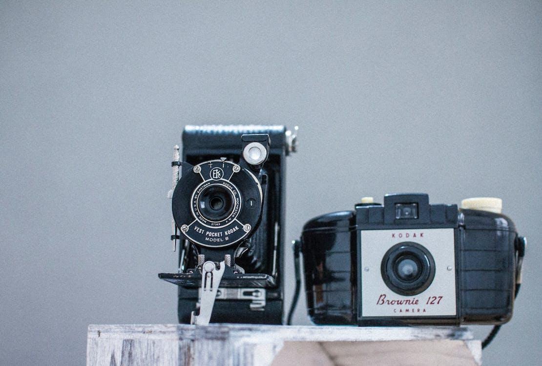 Two Black Cameras on Gray Board