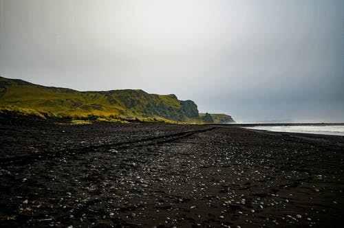 Black Sand Shore Near Green Grassy Hill
