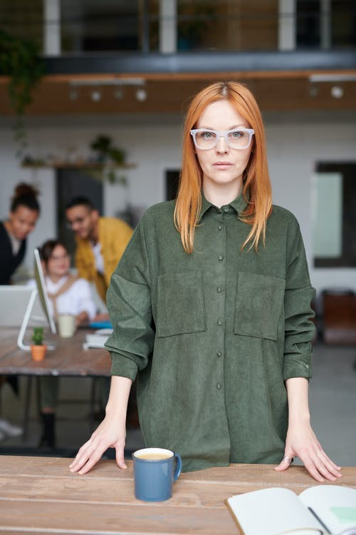 Woman in Green Collared Long-sleeved Top Standing Indoors