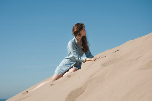 Woman in Blue Long Sleeve Shirt Sitting on Brown Sand