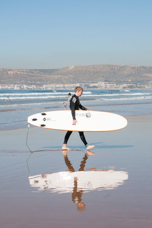 Woman in Black Wet Suit Carrying  White Surfboard on Beach