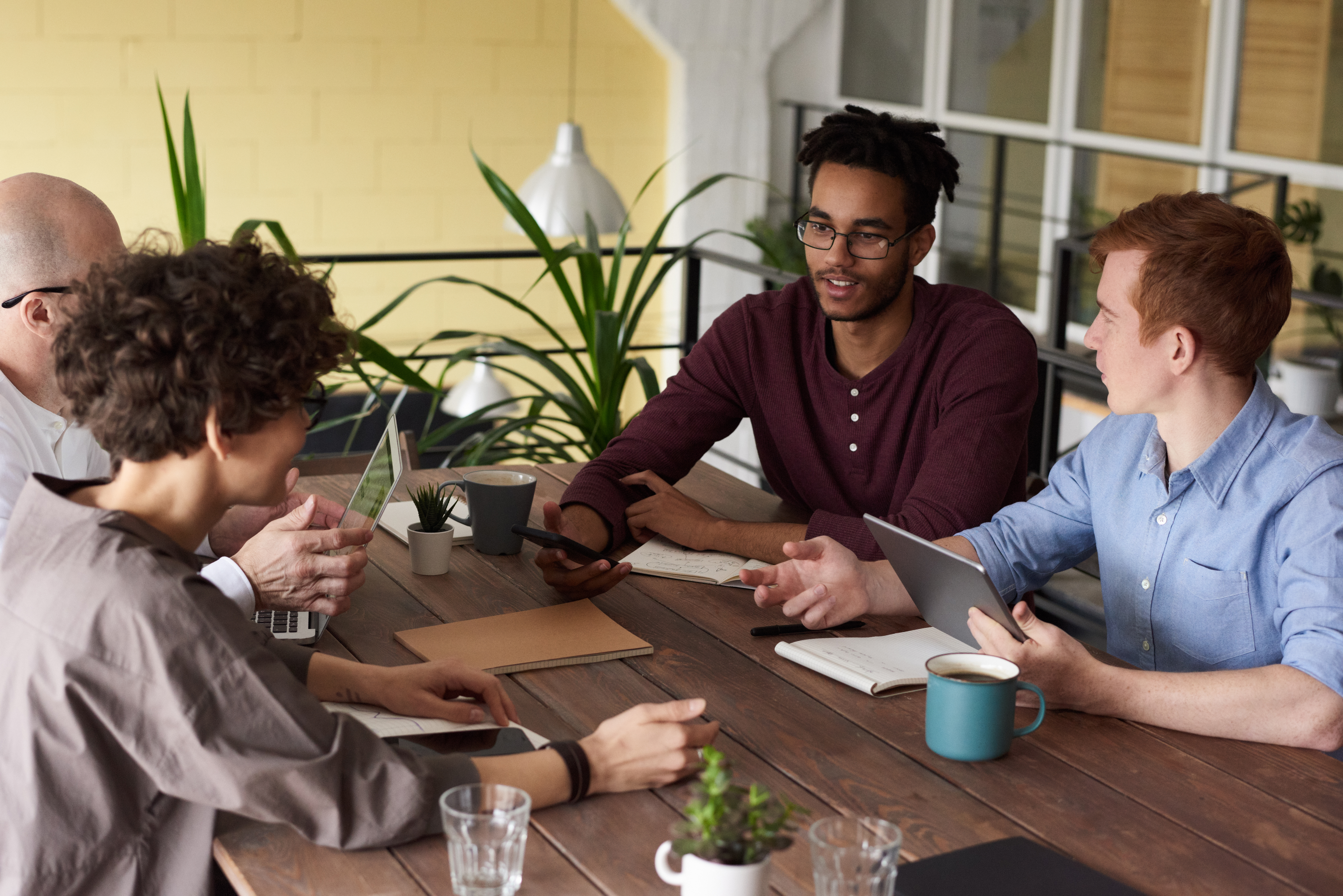 photo Of People Leaning On Wooden Table