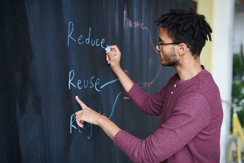 Photo Of Man Writing On Blackboard