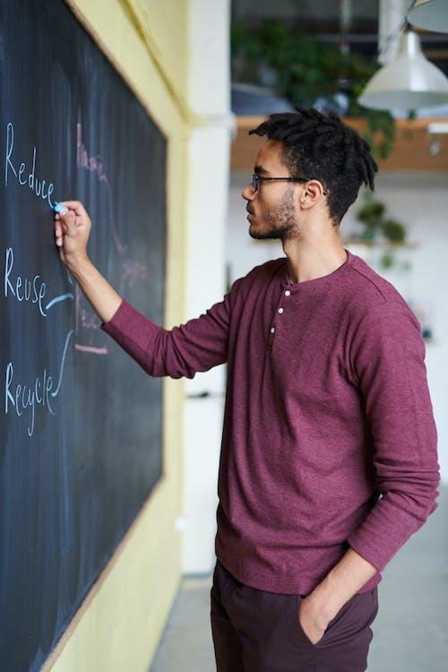 Man Wearing Purple Top and Pants Writing on Chalkboard